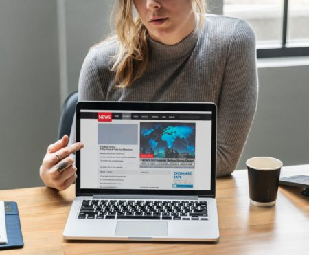 woman points to laptop screen showing news site for a small business blog