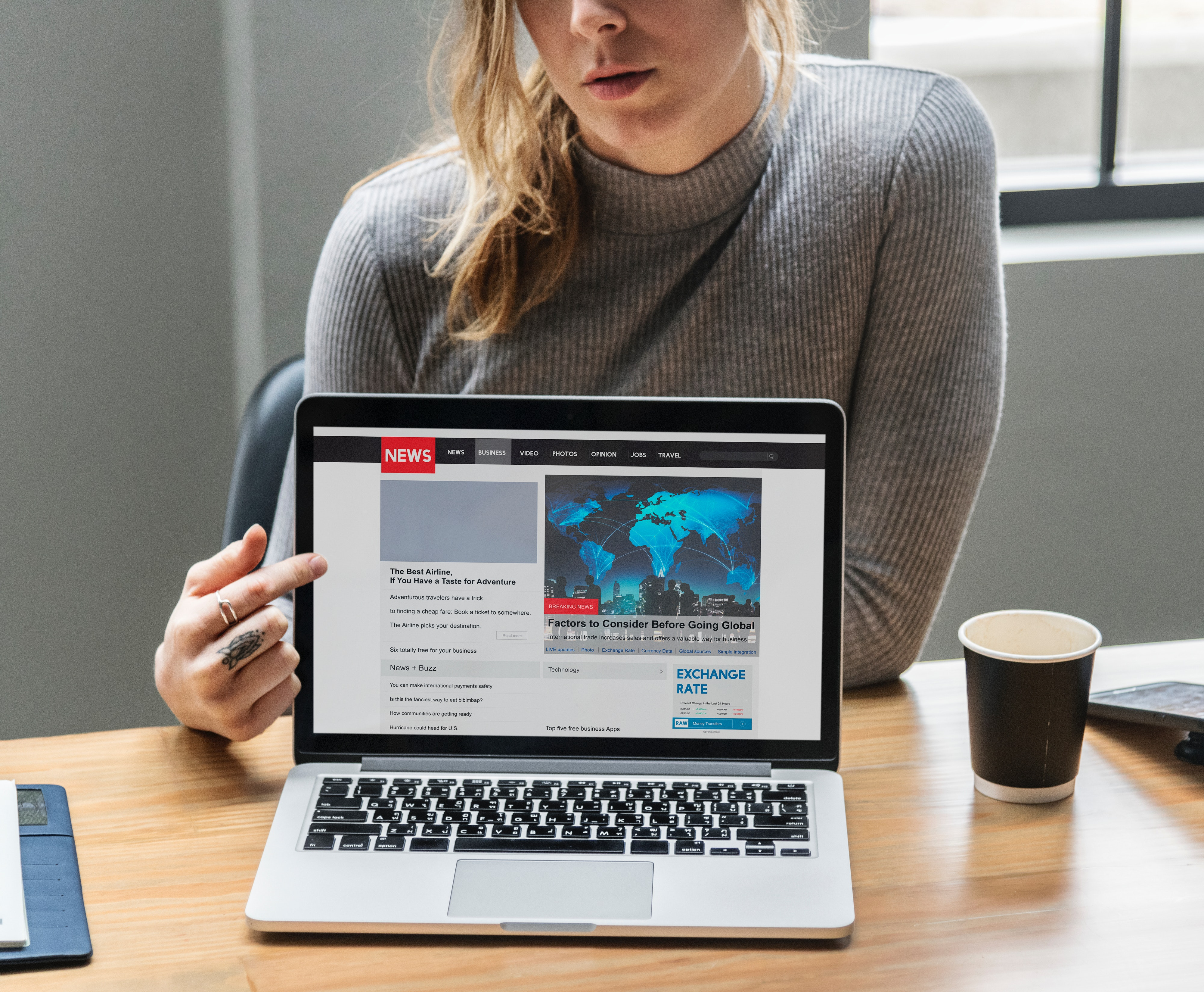 woman points to laptop screen showing news site
