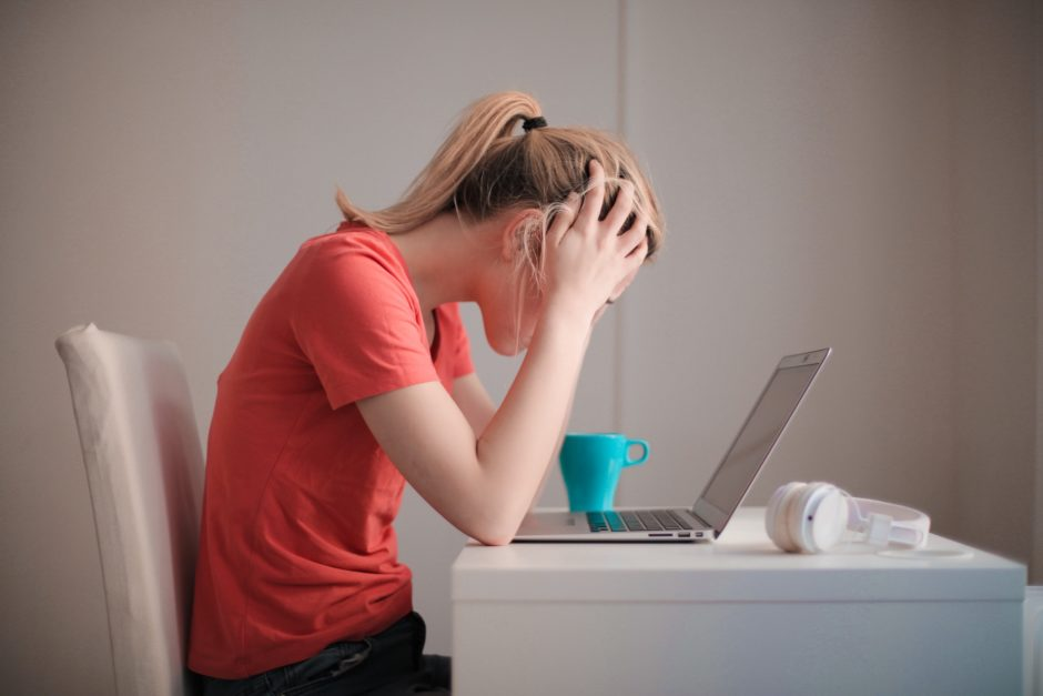 woman holding her head looking at her laptop