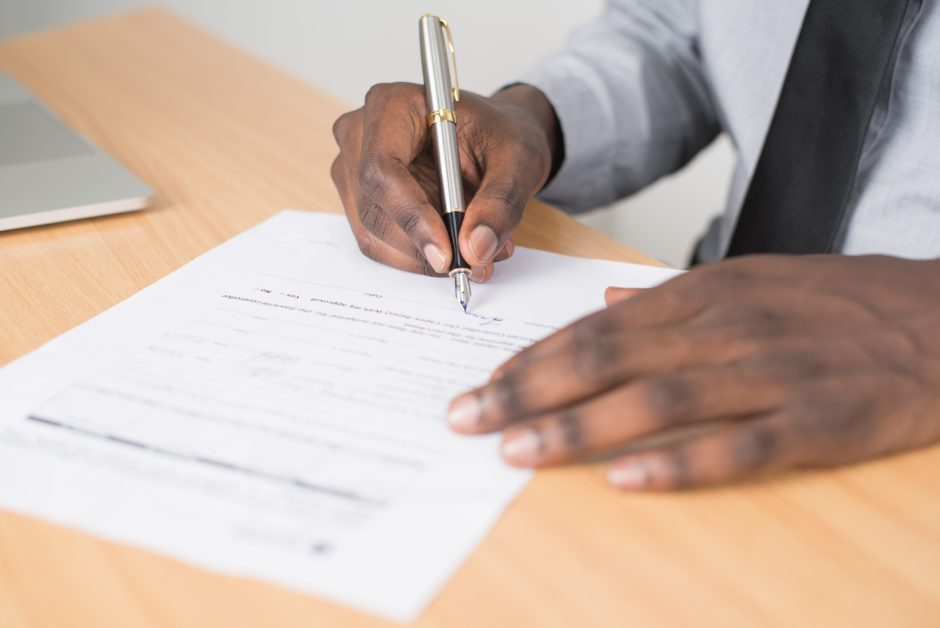 hands holding a pen signing a contract