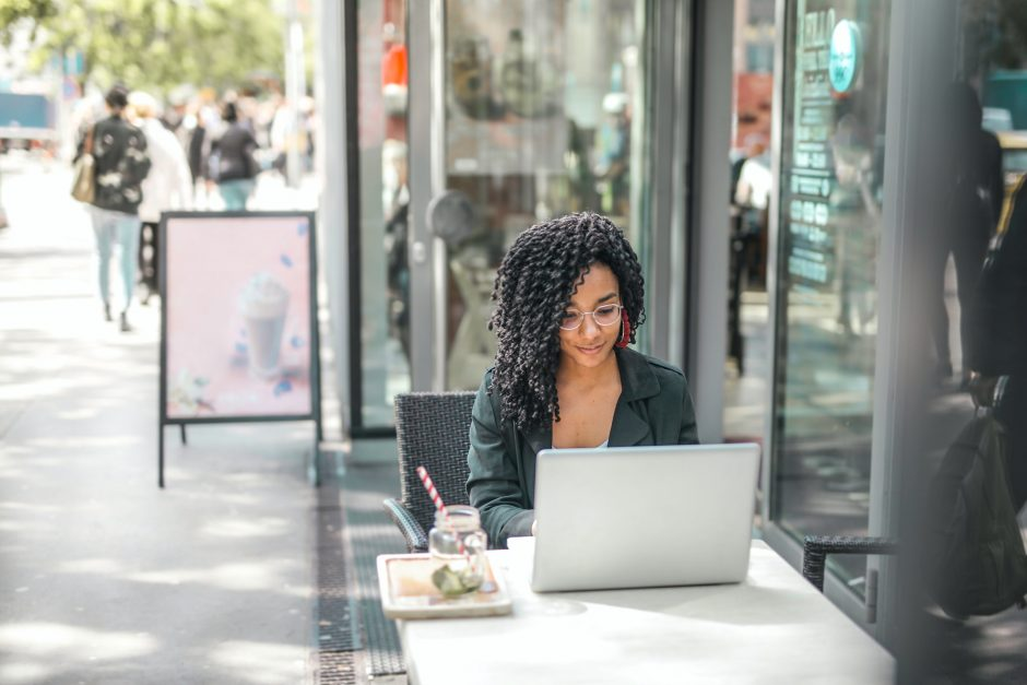 woman working on a laptop outdoors at a coffee shop
