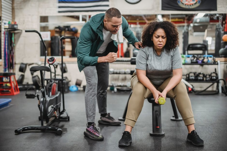 a man who is a personal trainer encourages a woman sitting on a bench in a gym